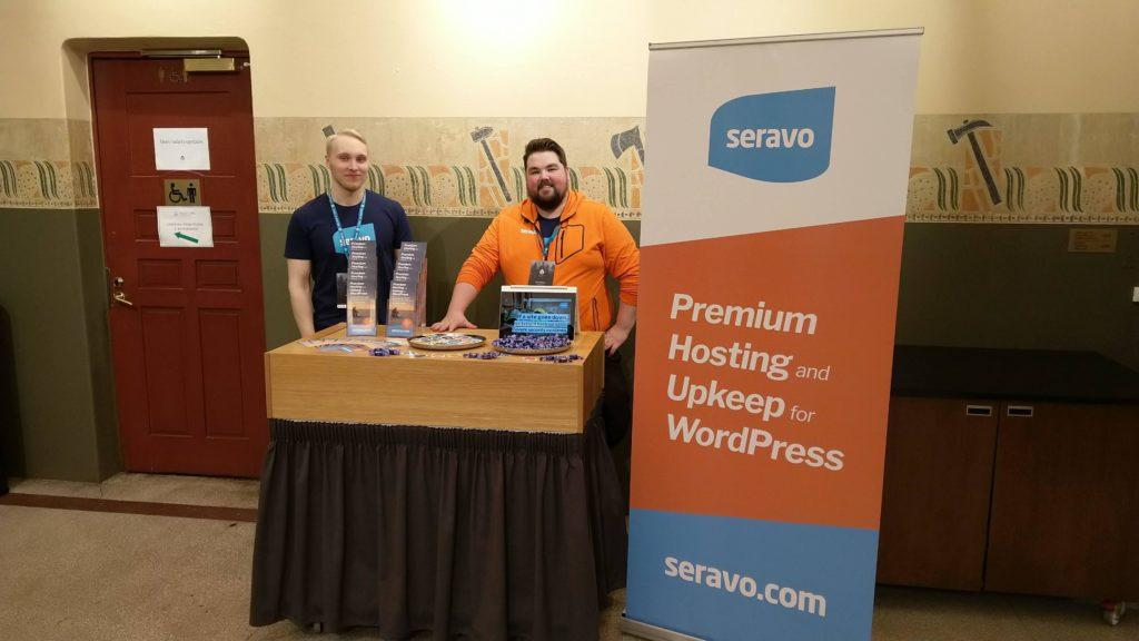 A picture of Seravo's sponsor booth with two people.